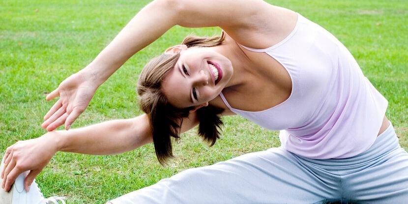 Девушка-делает-растяжку-на-траве-тренировки-в-радость-вместе-со-школой-диетологов-при-Академии-Wellness-Consulting