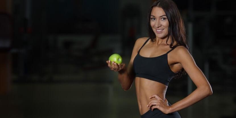 Девушка-тренер-по-питанию-с-яюлоком-в-руках-диетология-в-фитнесе-и-спорте-Академия-Wellness-Consulting