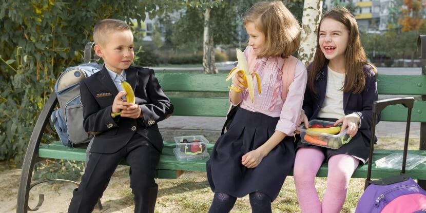 Школьники-едят-бананы-на-лавочке-питание-для-школьников-детская-диетология-Академия-Wellness-Consulting