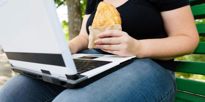 Девушка-ест-пирожок-и-смотрит-в-ноутбук-6-типов-ожирения-школа-диетологов-Академии-Wellness-Consulting