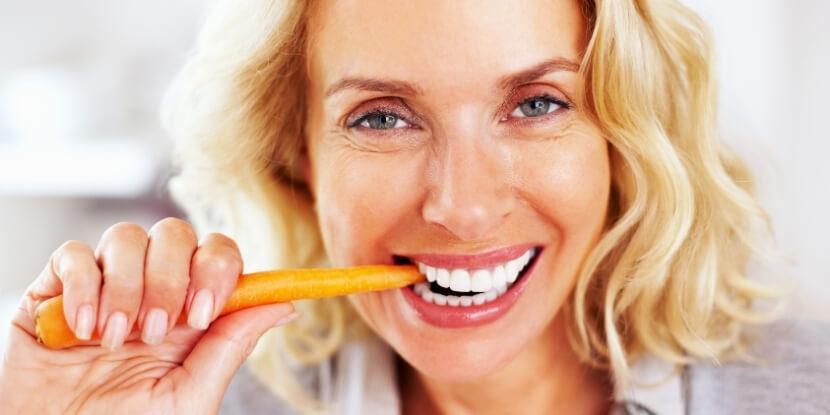 Женщина-кусает-морковку-постное-меню-советы-экспертов-школы-диетологии-Академии-Wellness-Consulting