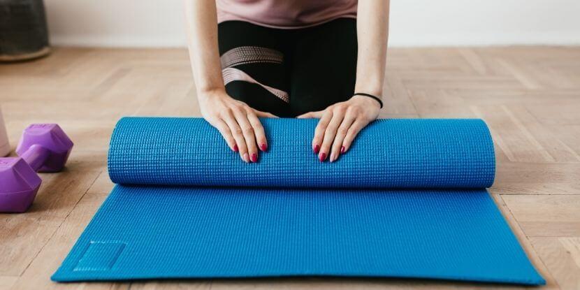 Девушка-сворачивает-фитнес-коврик-как-не-набрать-лишний-вес-на-удаленке-советы-школы-диетологов-Академии-Wellness-Consulting